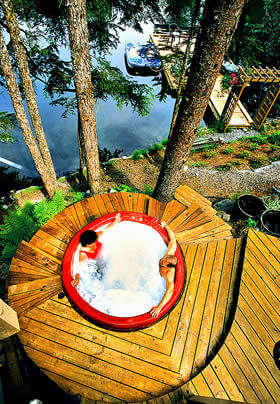 Photo of couple relaxing in a pondside outdoor hot tub at Pearson's Pond Luxury Inn and Adventure Spa.