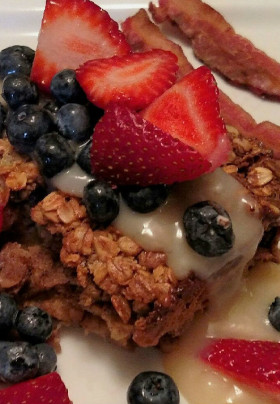Photo of Pearson's Pond special oatmeal bake with vanilla sauce, topped with berries and a side of bacon.